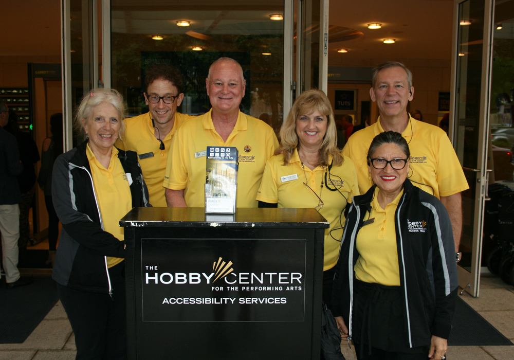 Access team wearing yellow polo shirts gathered around a device and black table with the Hobby Center Accessibility Services Logo on it