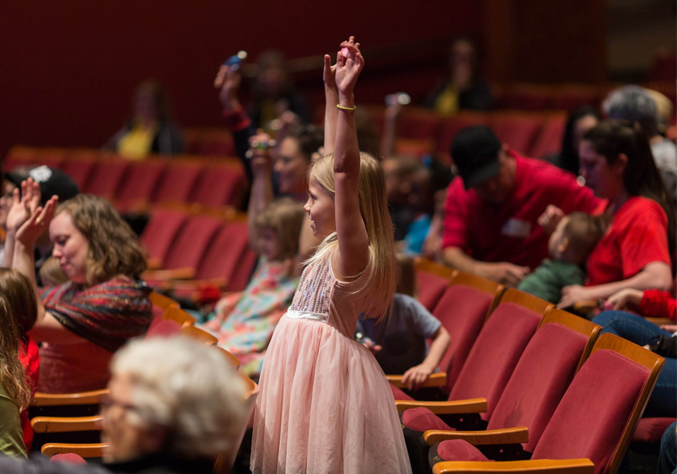 Young girl in a pink dress has hands raised in excitement as she stands within the crowds of the red, performance seats