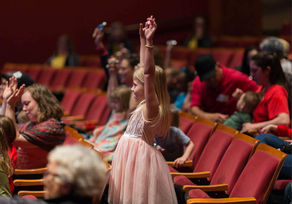 Girl standing in the audience with her arms raised above her head
