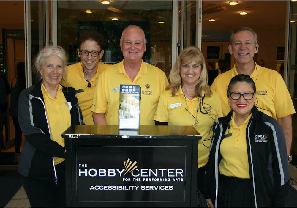 Hobby Center staff standing for a photo in front of a Hobby Center stand