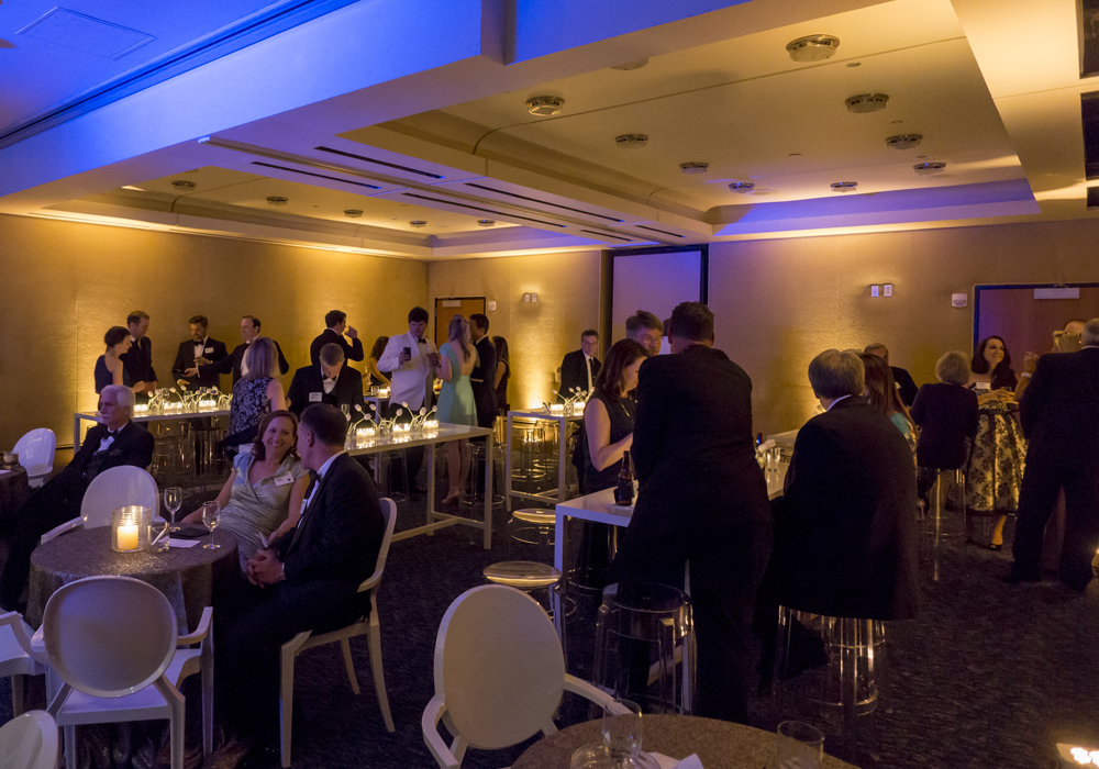 Group congregating in the dimly lit Founders Club around tables and chairs