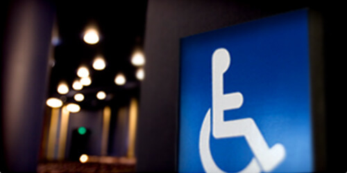 Wheelchair symbol hanging on a dimly lit wall with Hobby Center ceiling lights in the background