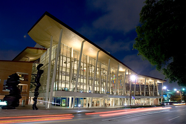 View of the Hobby Center building in evening with the exterior lights illuminating the windows