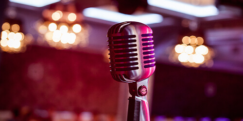 Retro microphone with pink and red mood lighting featured in a lounge