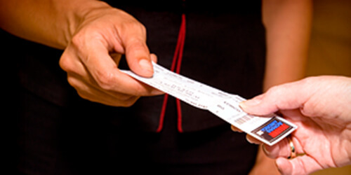 Two people's hands exchanging a ticket from one person to the other